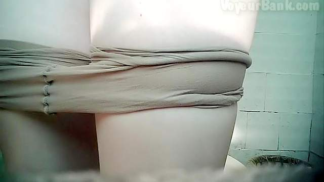 Pissing beauty is playing with her pussy in the toilet