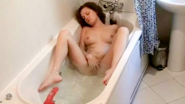 Curly brunette is sucking her dildo in the bath
