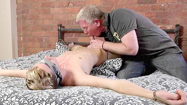 Bound gay boy nearly covered in hot wax