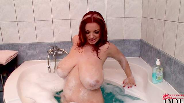 Redhead babe Joanna Bliss is poking her puss in the bath