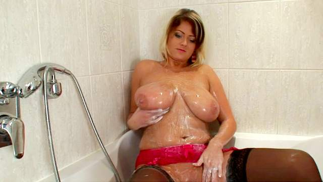 Blonde Lola is watering her sexy boobies